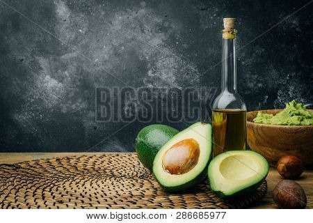 Avocado And Avocado Oil On A Wooden Background. Copy Space.