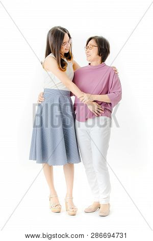 Full Length Shot Of Happy Aged, Senior Asian Mother Holding Young Beautiful Attractive Daughter On W