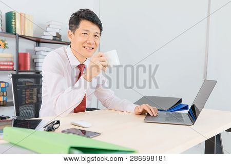 Portrait Of Middle Aged, Handsome, Asian, Businessman, In White Shirt, Dark Red Necktie, Working In
