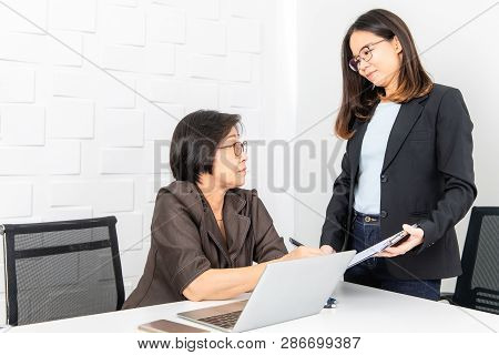 Studio Shot Of Asian, Senior Businesswoman With Laptop, Sitting With Young Staff In Board Room In Of