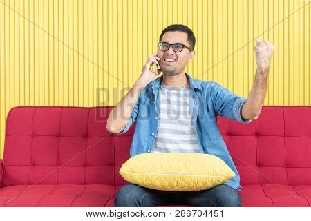 Shot Of Young Asian Handsome Bearded Man Sitting On Red Sofa And Talking On Smartphone, Making Victo