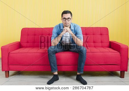 Close-up Of Young Asian Handsome Bearded Man, Wearing Eyeglasses In Denim Shirt, Sitting On Red Sofa