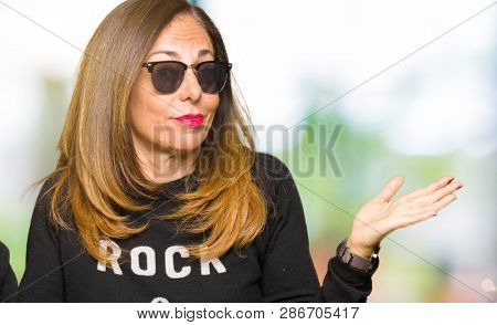 Beautiful middle age woman wearing sunglasses and rock and roll sweater clueless and confused expression with arms and hands raised. Doubt concept.
