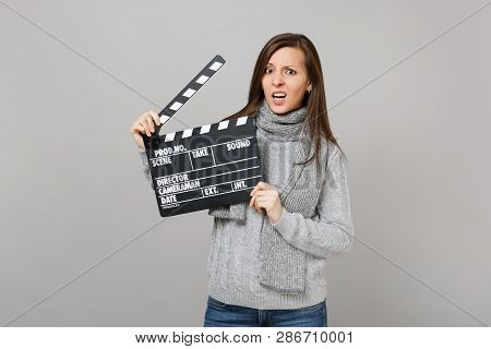 Perplexed young woman in gray sweater, scarf hold classic black film making clapperboard isolated on grey background. Healthy fashion lifestyle people emotions cold season concept. Mock up copy space. poster