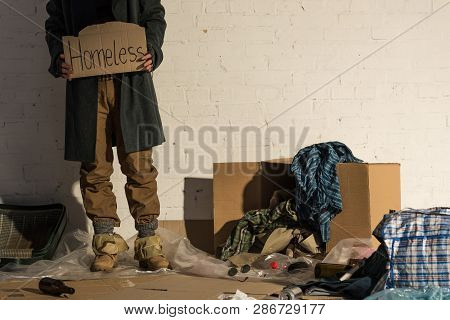 Partial View Of Homeless Man Standing On Garbage Dump And Holding Piece Of Cardboard With Homeless H