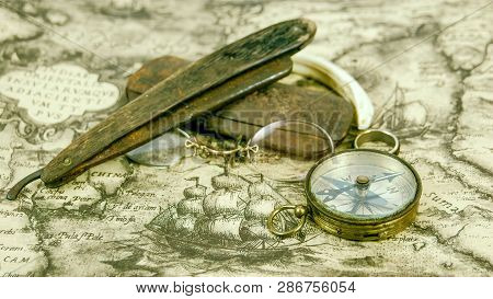 Few Navigators Things And A Compass On The Map. The Eyeglass Wooden Razor And A Ring