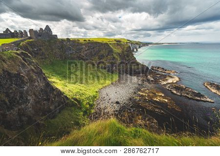 Northern Ireland shoreline with Dunluce castle in the distance. Picturesque grass covered lowland and the steep cliffs under the grey cloudy sky. Amazing Irish bay before the rain. Wild virgin nature.