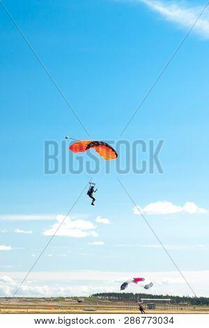 Two Parachutists Are Landing On Colorful Parachutes To Aerodrome.