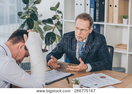 Worker With Broken Arm Sitting At Table And Reading Documents Opposite To Businessman In Blue Jacket