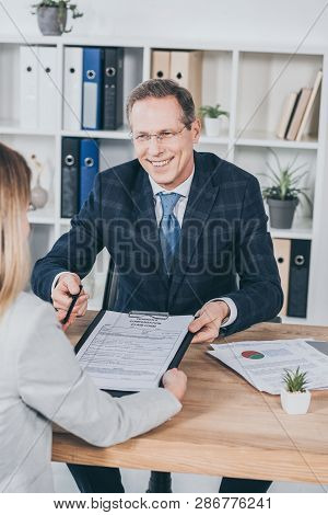 Businessman Giving Woman Pen And Form For Compensation Claim Over Table With Laptop In Office, Compe