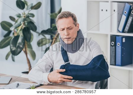 Middle Aged Worker Holding Broken Arm Wile Sitting At Table With Document In Office, Compensation Co
