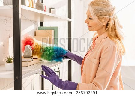 Senior woman in rubber gloves cleaning shelves with duster poster