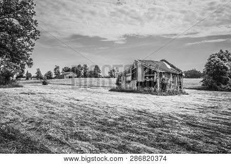 Old Barn In A Hayfield.with Cloudy Skies