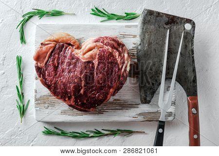 Heart shape marbling ribeye steak on white plate. Prime rib beef chop