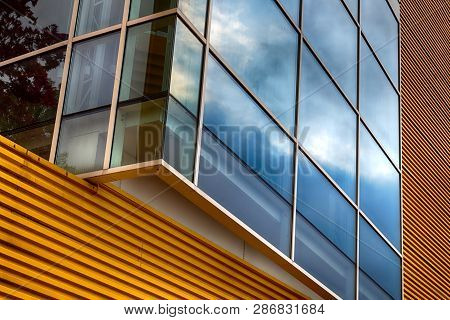 Abstract Yellow Modern Building Exterior With Glass Window In Daylight