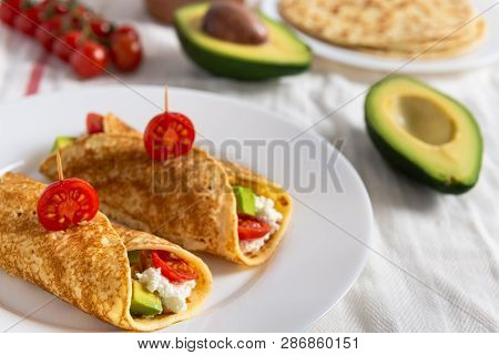 Crepe Pancakes With Avocado, Soft White Cheese And Cherry Tomatoes On White Plate. Cherry Tomatoes,