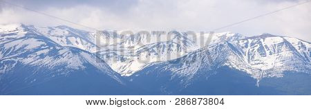 Panorama of a mountain range with snowy peaks. Spring landscape with melting snow in the mountains