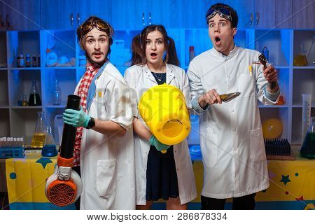 Surprised Young Funny Scientists Standing In The Laboratory And Looking At Camera.