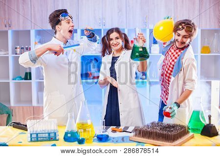 Cheerful Young Laboratory Assistants Standing With Chemistry Equipment.
