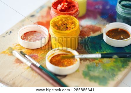On The Palette, Painted In Different Colors, There Are Jars Of Gouache Paint And Brushes Are In Disa