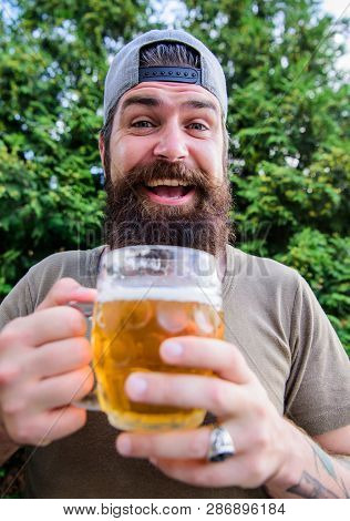 Man relaxing enjoying beer hot summer day. Beer and ale concept. Quench thirst. Hipster brutal bearded man hold mug cold fresh beer. Craft beer is young, urban and fashionable. Alcohol drink and bar poster