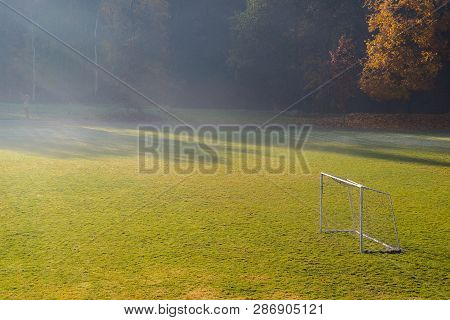 Early Morning In The Amatuer Soccer Field. Football Game Playground In Autumn Foggy Morning. Early M