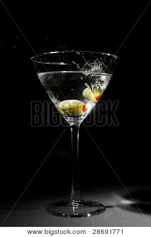 Two Green Olives Splashing Into Martini Glass