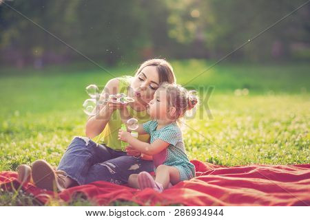 Happy Childhood - Mother And Cute  Child Blows Soup Foam And Make Bubbles
