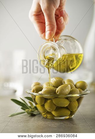 Organic Olive Oil. Bottle Of Extra Virgin Oil Pouring In To Glass Bowl With Olives