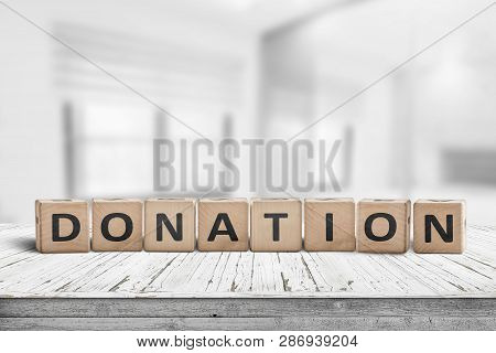 Wooden Donation Sign On A Worn Desk In A Bright Room With Lights
