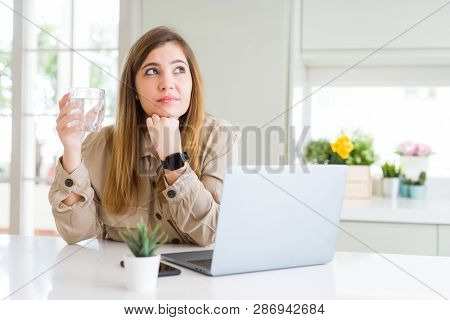 Beautiful young woman working with computer takes a break to drink glass of water serious face thinking about question, very confused idea