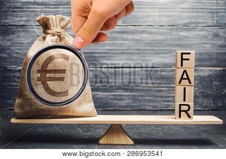 Euro Money Bag And Wooden Blocks With The Word Fair. Balance. Fair Value Pricing, Money Debt. Invest