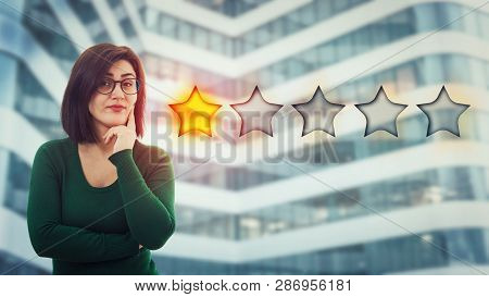 Skeptic Young Woman Holding Hand Under Chin Looking Disappointed Choosing One Star Rating. Bad And P