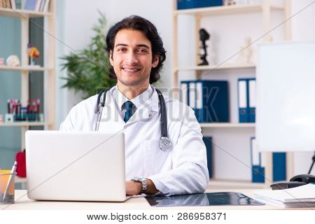 Young handsome doctor in telemedicine concept