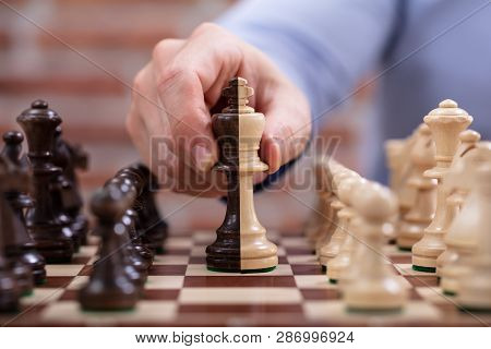 Person's Hand Moving A King Chess Piece