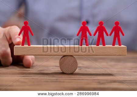 Businessperson Showing Imbalance Between Red Figures On Seesaw
