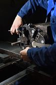 A worker in blue workwear performs maintenance on the CNC machine to install drills in the turret for working with metal. Hands of the worker close up, screw various drills poster