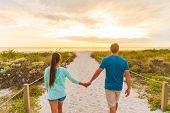 Happy young couple in love walking on romantic evening beach stroll at sunset. Lovers holding hands on summer holidays in Florida beach vacation destination. People walking from behind. poster
