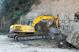 An Excavator Digs And Collects Soil And Stone For A Road Widening Project