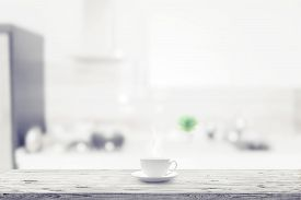 White Cup On Wooden Table Over Blured Kitchen Interior Background
