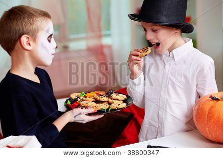 Photo of two eerie boys eating cookies on Halloween day