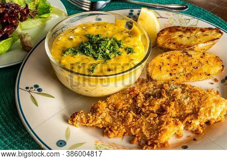 Batter-fried Fish With Sauce, Fried Potato, Lemon And Vegetable In White Ceramic Plate On Blue Table