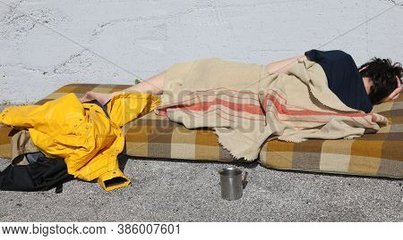 Poor Homeless Outcast Rests On A Dirty Mattress In The Street Of The Metropolis
