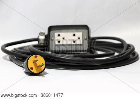 Yellow Plug And Out Focus Outlet With Black Cable On The White Background. Used For Electrical Conne