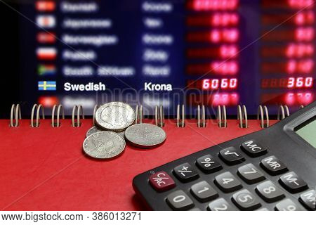 Heap Of Sweden Coins With Calculator On The Red Floor And Digital Board Of Currency Exchange Money B