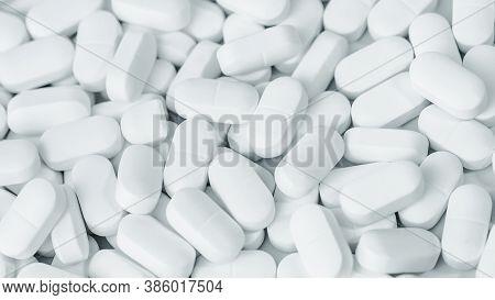 Medical Background Of Many White Capsule Tablets Or Pills On The Table. Full Frame Background. Healt
