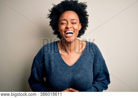 Young beautiful African American afro woman with curly hair wearing casual sweater smiling and laughing hard out loud because funny crazy joke with hands on body.