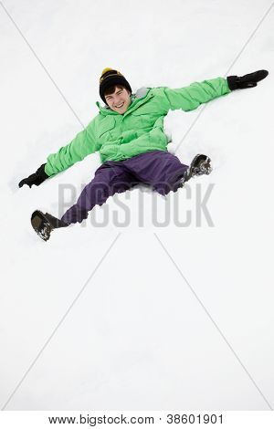 Teenage Boy Making Snow Angel On Slope