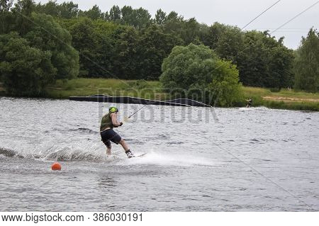 A Wakeboarder On A Wakeboard Landed In The Water, Surrounded By Splashes. Two Men Wakeboarding On Th