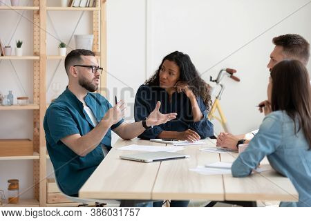 Diverse Employees Listening To Confident Businesswoman Mentor At Meeting